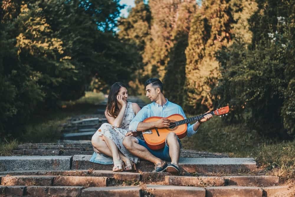 man singing while playing a guitar sitting on the stair with a woman