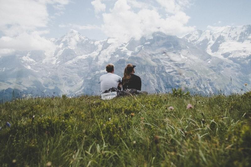 man sitting beside woman on grass facing mountains