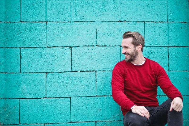 man in red sweater sitting near blue wall