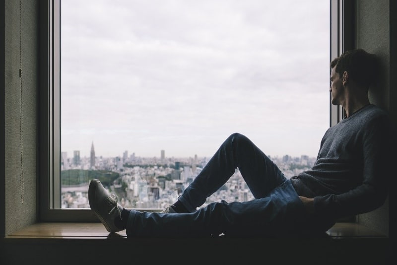 man sitting near window while looking at city