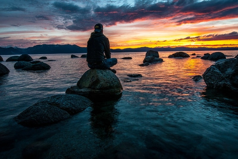 man with cap sitting on rock looking at sea