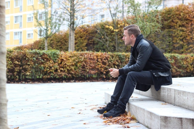 man wearing black jacket sitting on stair steps