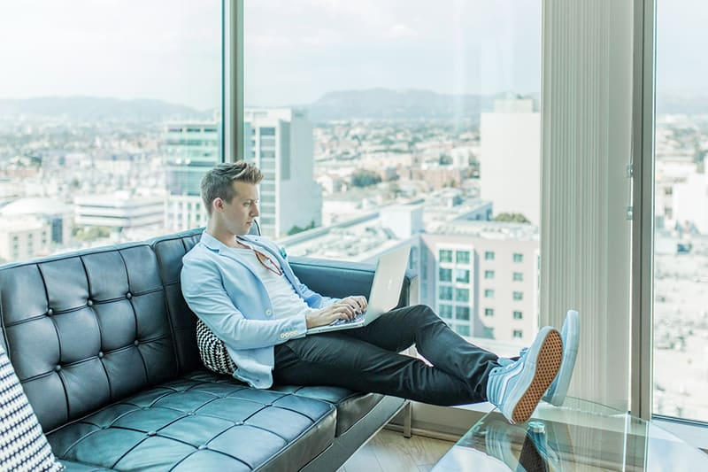 man sitting on the sofa using the laptop