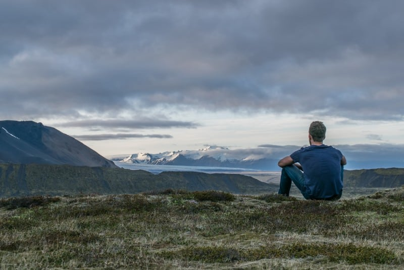 man sitting on top of hill looking at mountain