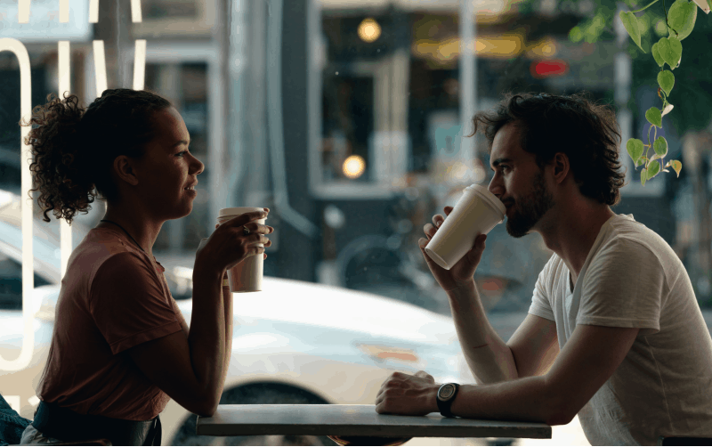 man standing in front of woman at a table near a window while drinking coffee during daytime