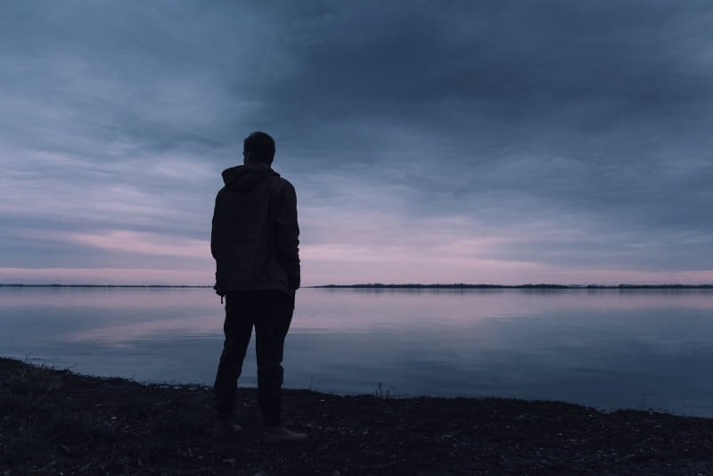 man in black jacket standing in front of lake