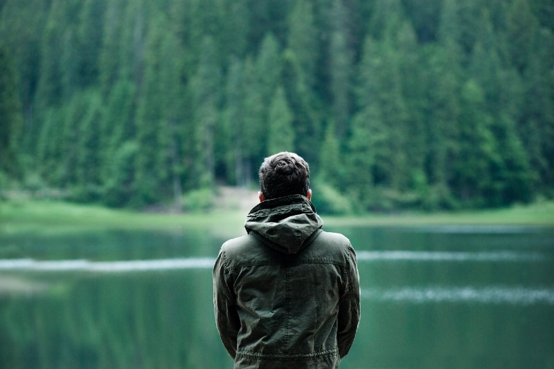 man in hooded jacket looking at water