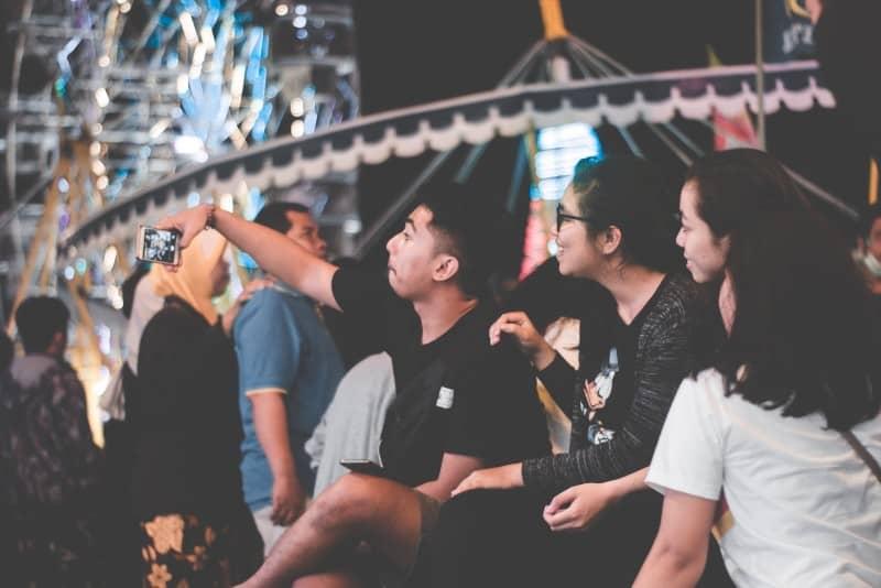 man in black shirt taking selfie in amusement park