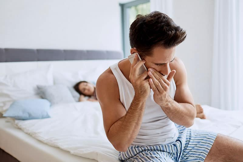 man talking on phone hiding from woman