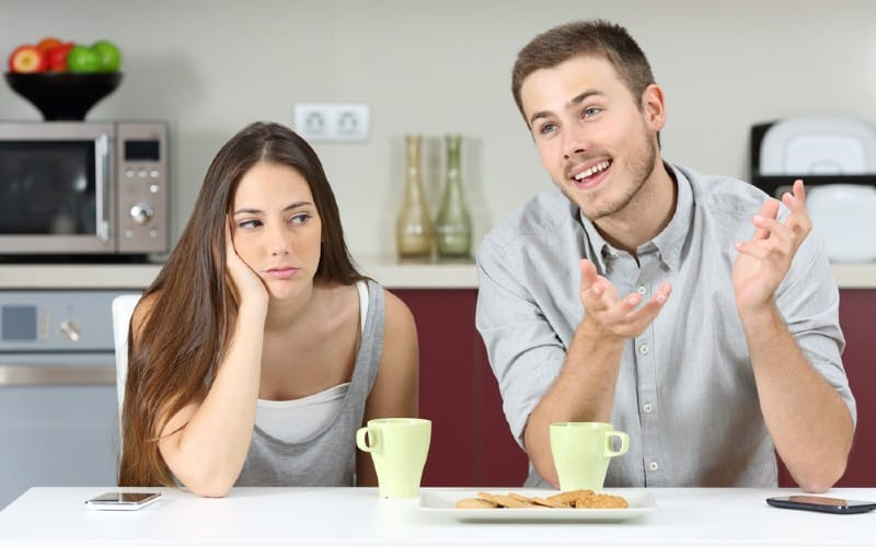 Man talking to bored woman while sitting beside her in front of a table with coffe cups and cookies