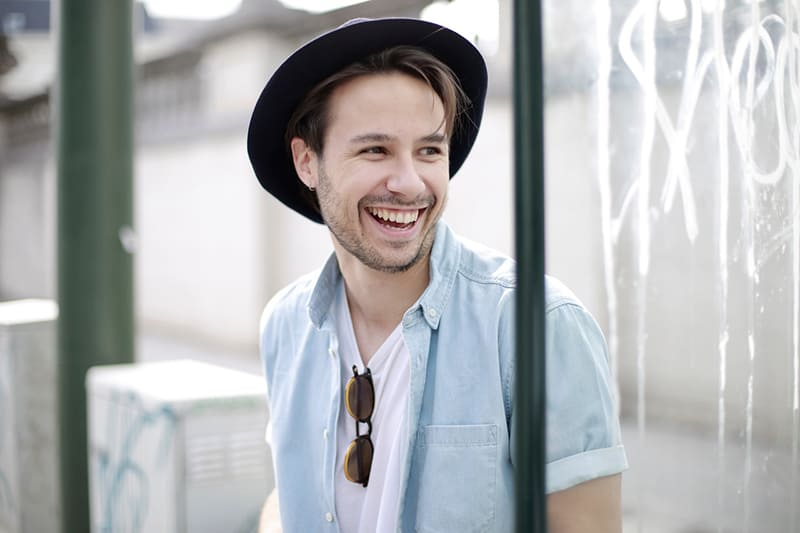man wearing black hat while he is smiling