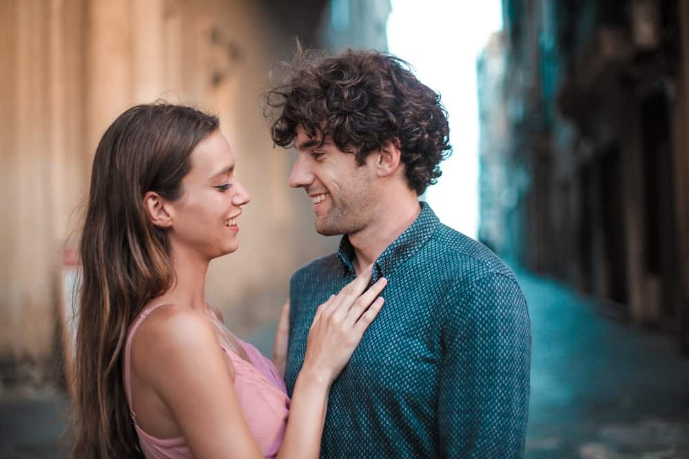 man wearing blue shirt kissing woman in a pink tank top