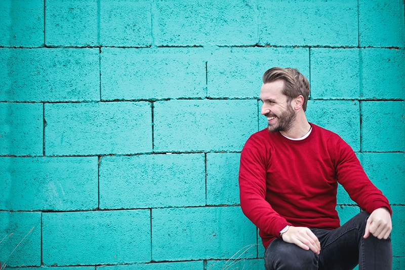 man wearing red sweatshirt while leaning on the wall