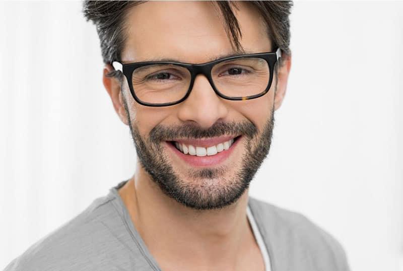 man with beard smiling wearing eyeglasses and gray shirt