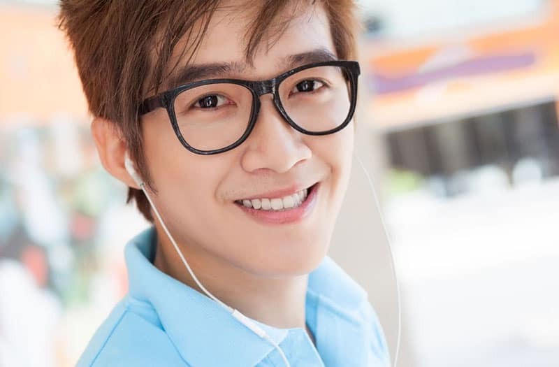 man with earphones with eyeglass smiling
