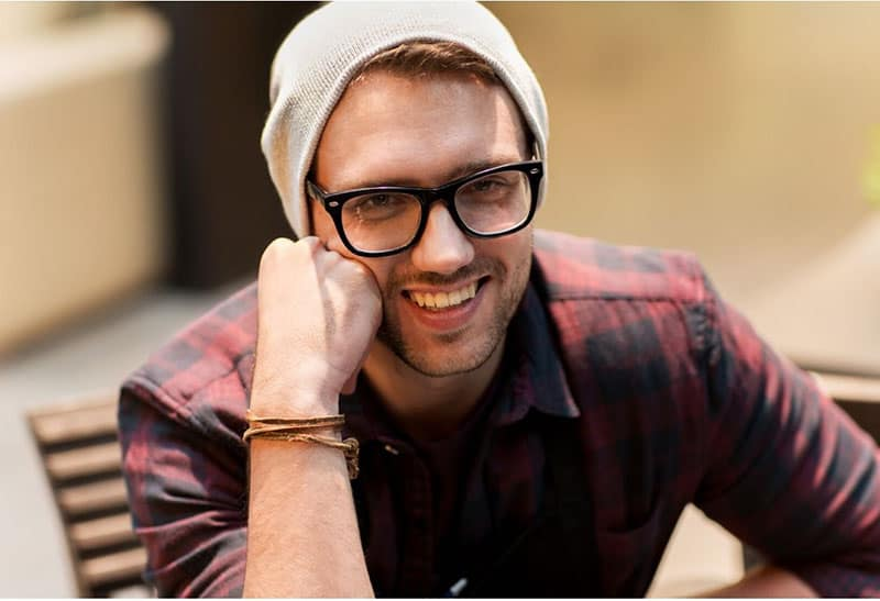 man with fist on his face smiling wearing a bonnet, eyeglass and checkered top