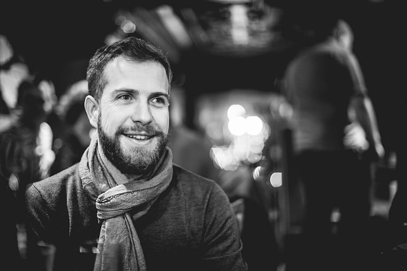 man with scarf smiling