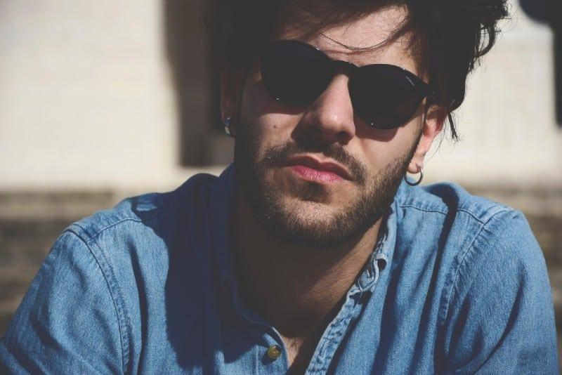 man in denim shirt and black sunglasses sitting outdoor