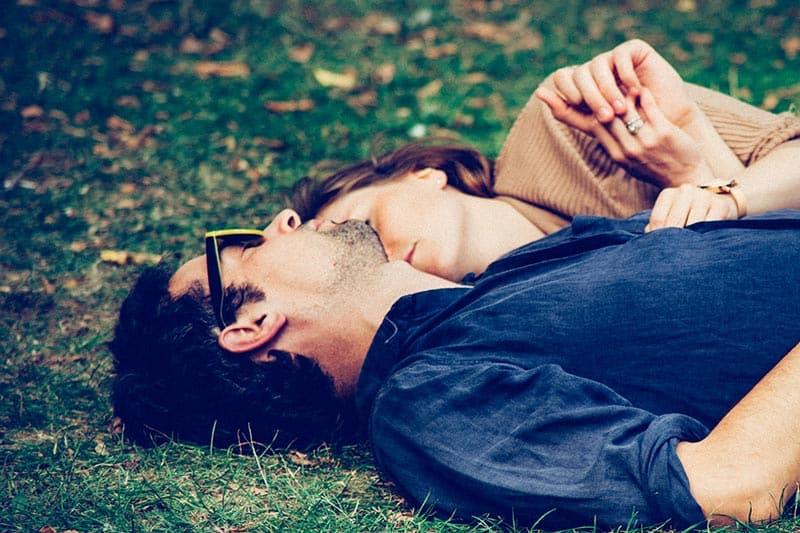 Man and woman lying on grass hugging