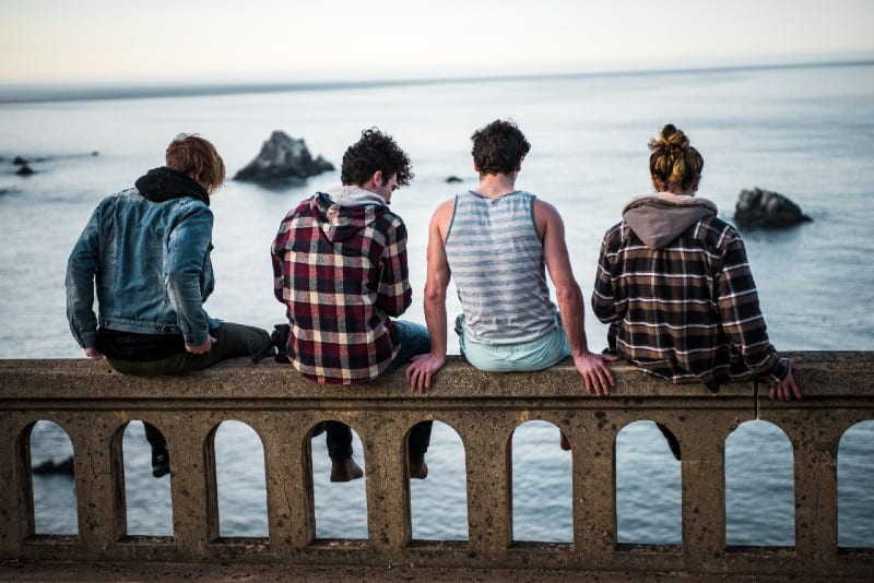 four men sitting on concrete bench and looking at water