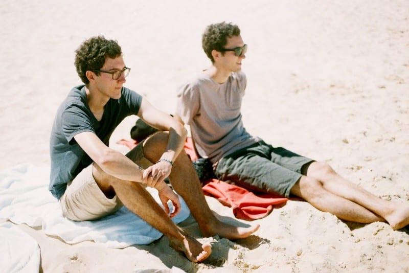 twin males sitting on beach