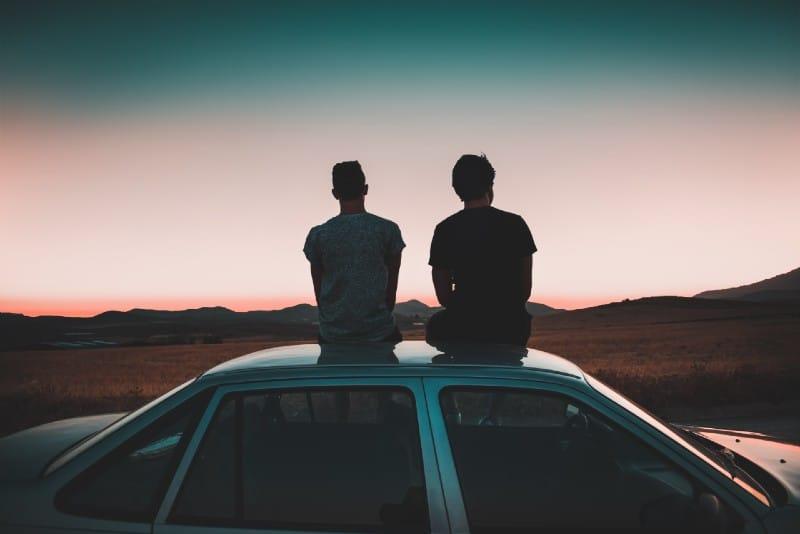 two men sitting on vehicle during sunset