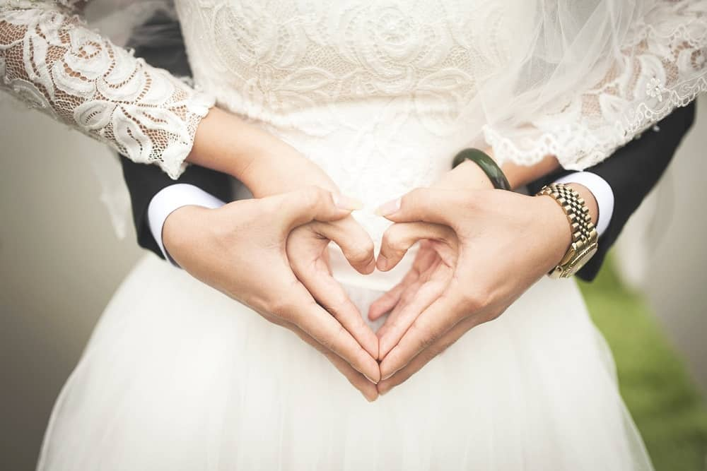 midsection of married couple making heartshape hands
