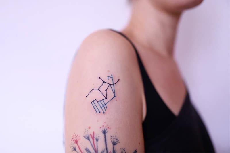 minimal shoulder Virgo tattoo with blue details