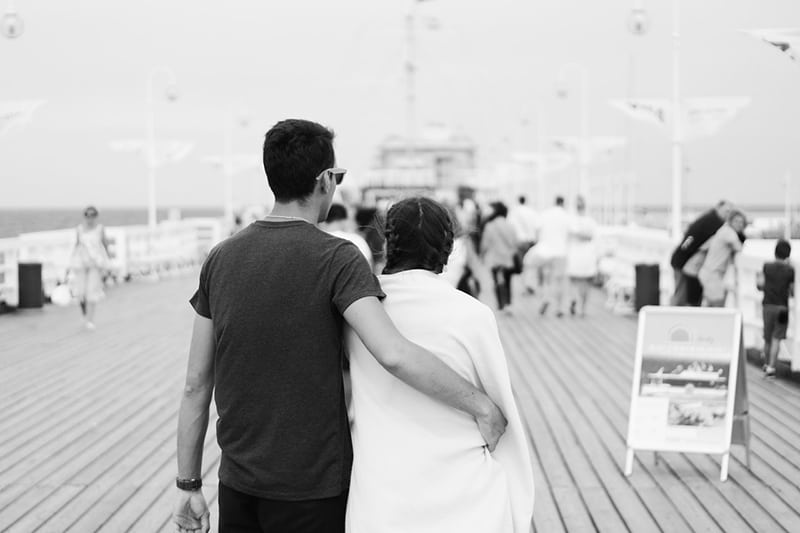 Monochrome couple man hug woman on boardwalk