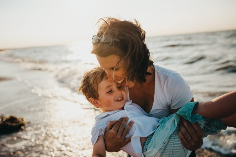 woman holding boy near water