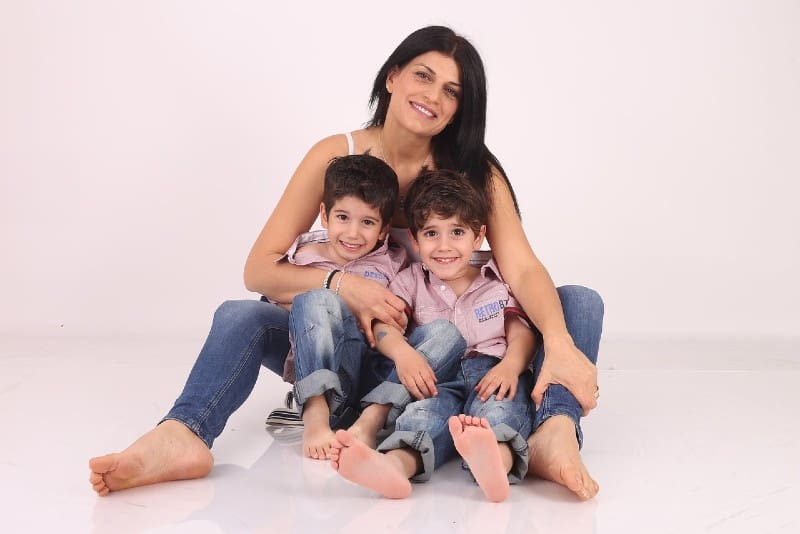 mother sitting on floor with male twins