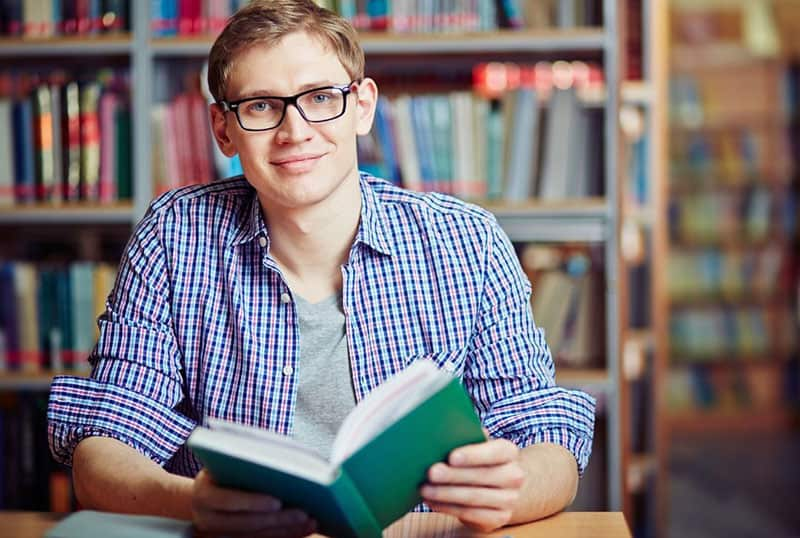 nerd guy holding a book inside a library