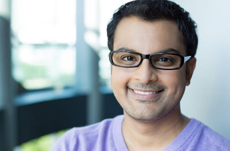 nerd man smiling in purple shirt