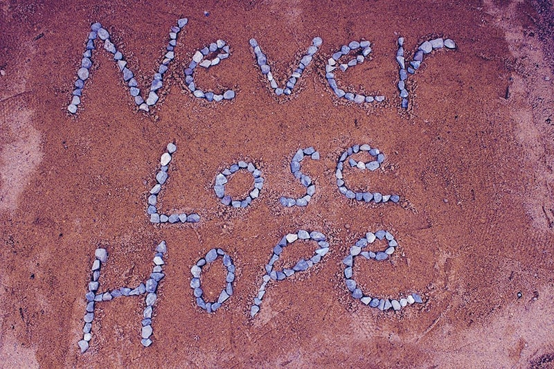 never lost hope quote made with stones on brown background