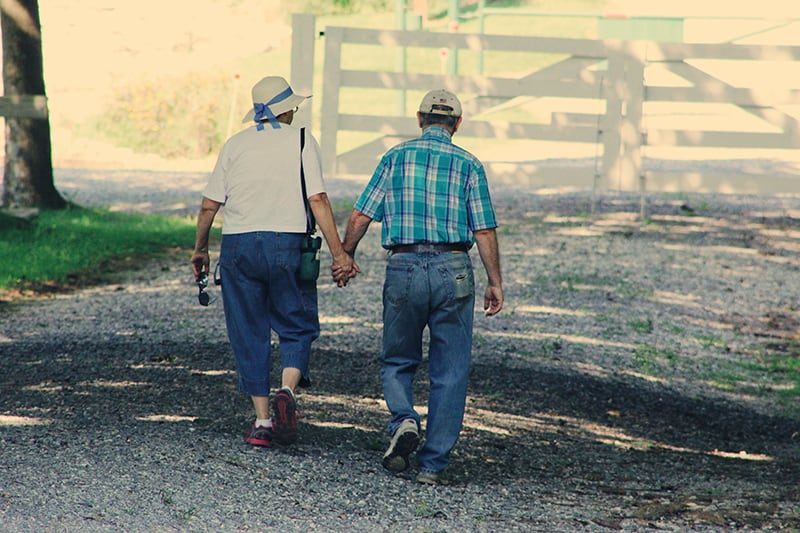 old couple walking whole holding hands