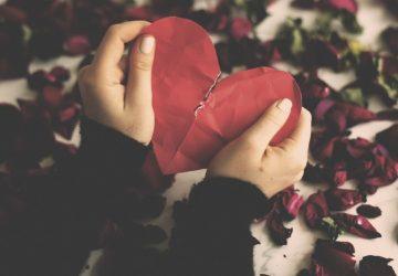 Hands holding red paper broken heart