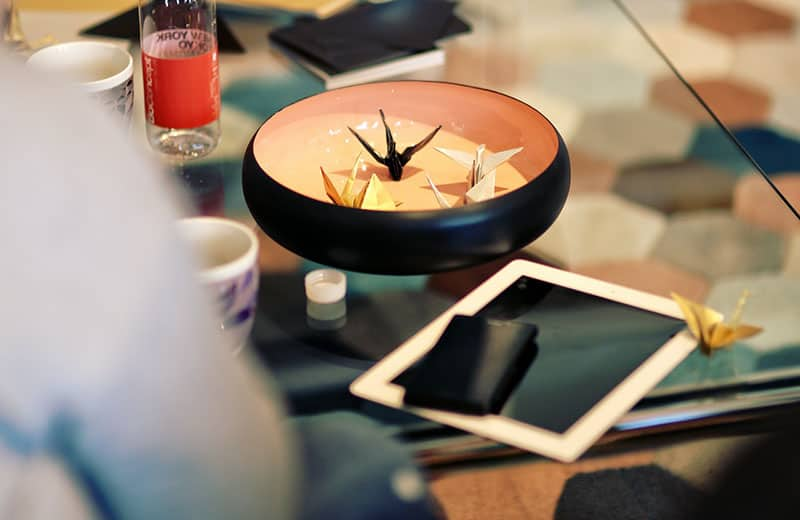 origami in vessel form placed in a bowl with a tab, both in the table