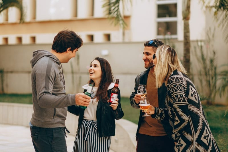 four people having drinks while standing outdoor