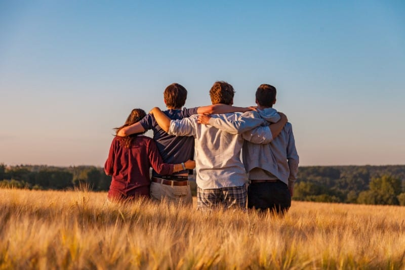four people standing and hugging in the field