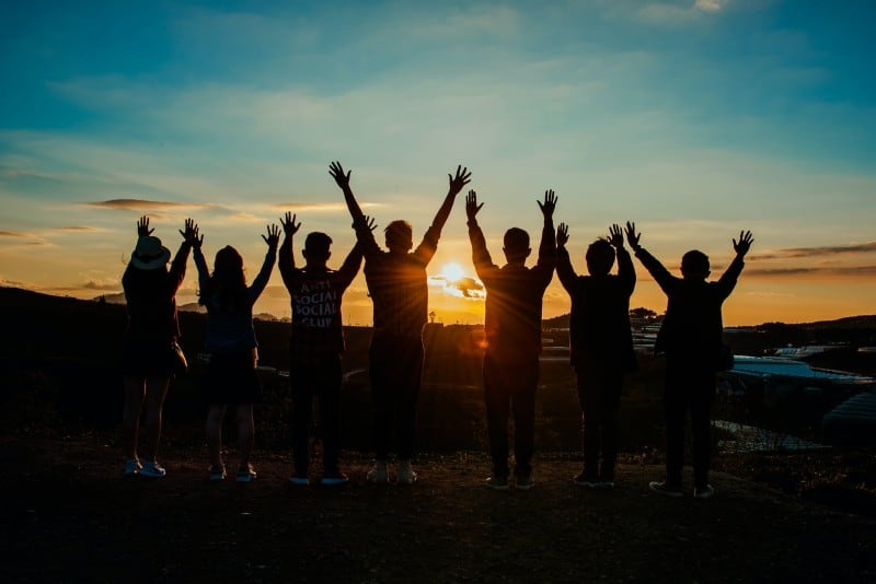 seven people put hands up during sunset