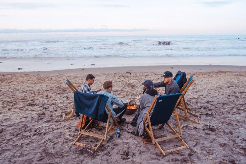 three men and one woman sitting on beach lounge near bonfire
