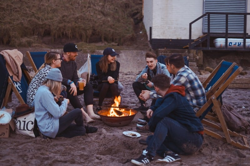 group of people sitting by bonfire at beach