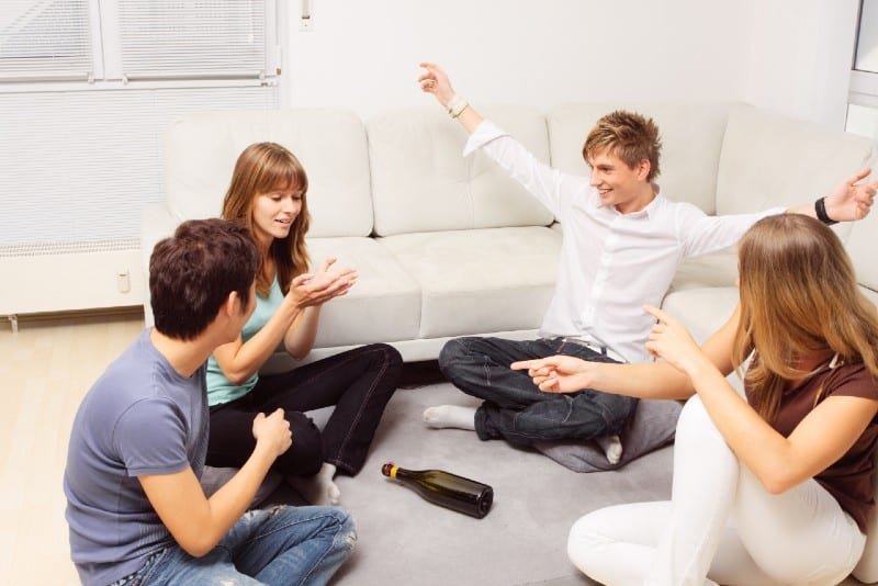 four people sitting on carpet and playing truth and dare
