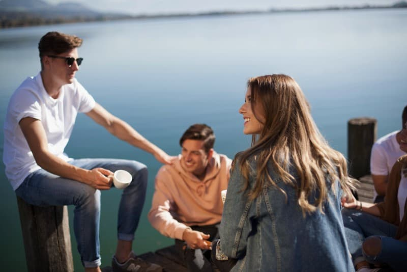 group of people sitting on dock and talking