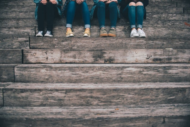 four people sitting on wooden stairs