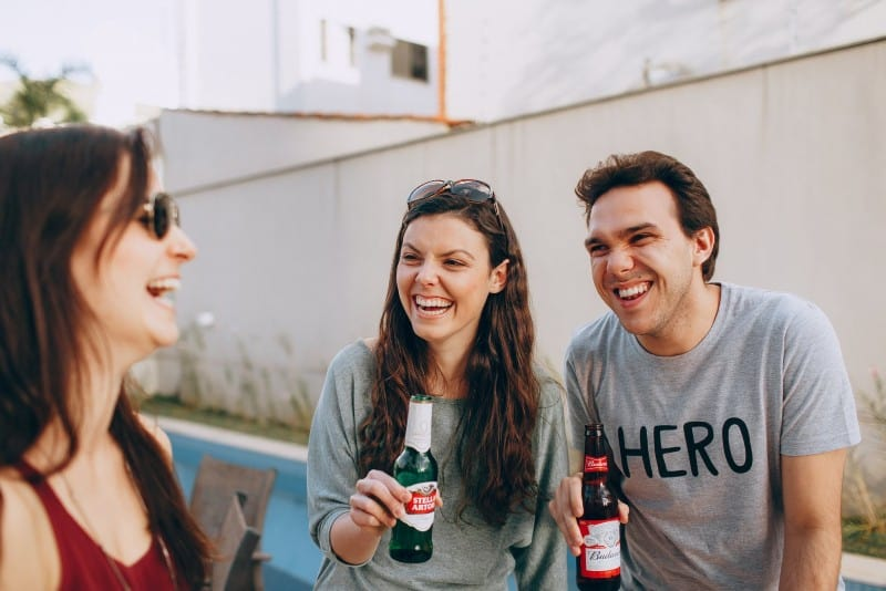 three people smiling and drinking outdoor