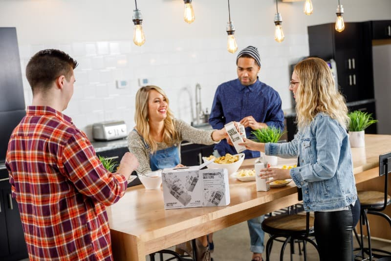 four people standing near kitchen table