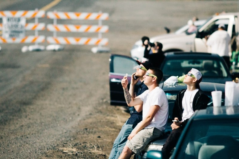 group of people sitting on car while watching eclipse