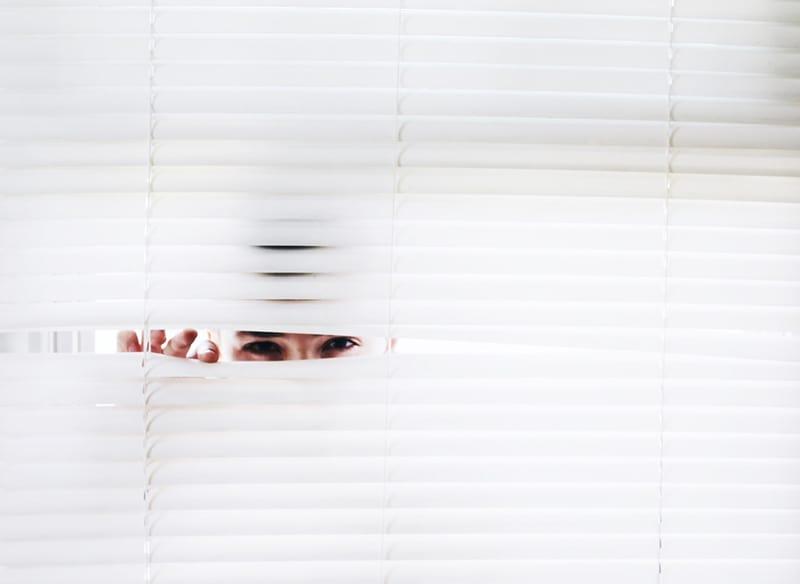 person peeking trough the sunblind