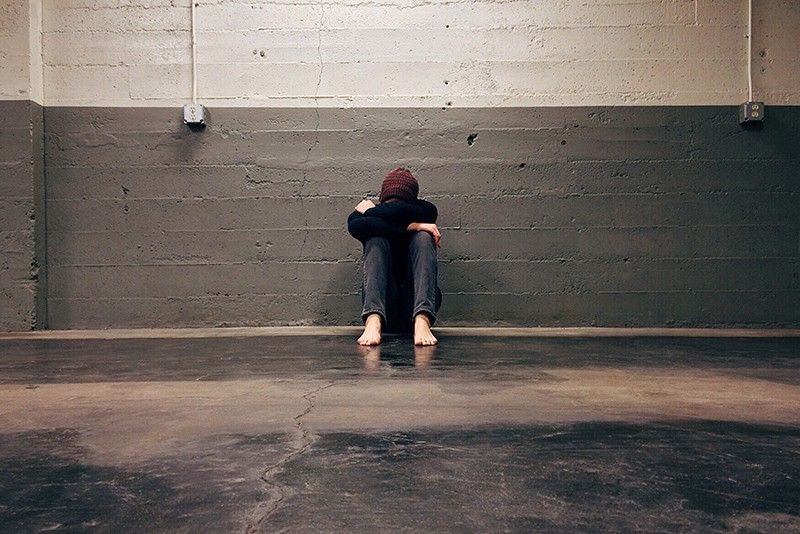 person sitting alone on the floor near concrete wall